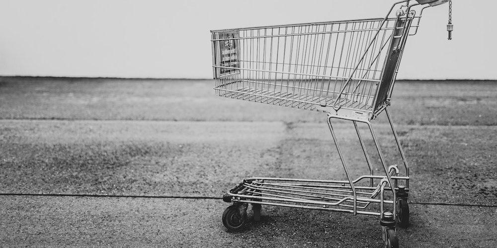 Caddie de courses vide sur fond gris neutre